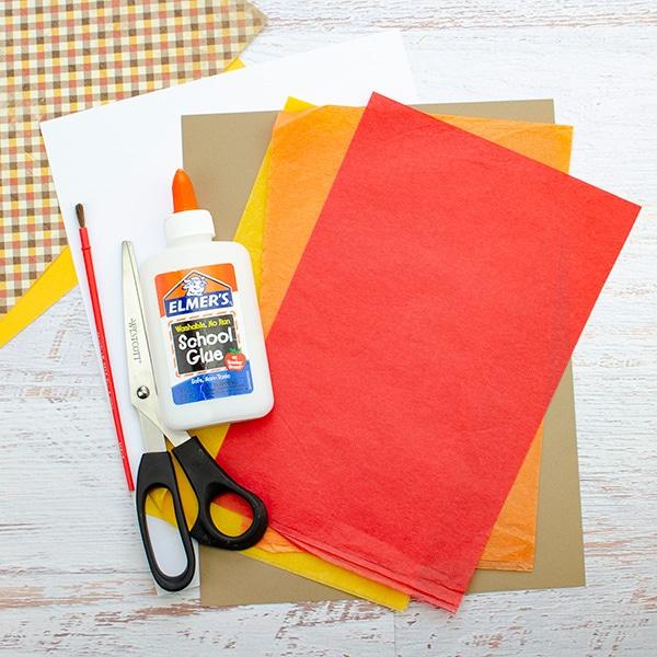 tissue paper, construction paper, white glue, scissors, paintbrush