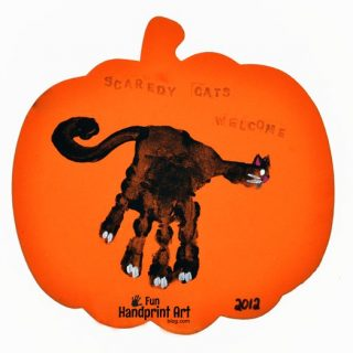 Handprint Halloween Sign Craft For Kids: 'Scaredy Cats Welcome' featuring a black cat handprint on a foam pumpkin.