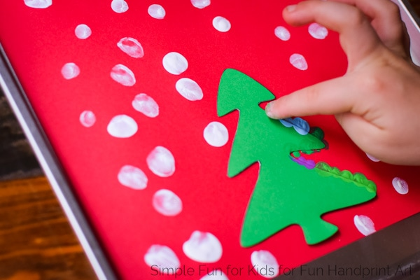Have you tried the fingerprint resist technique? It's super simple for kids of all ages and comes out looking great! Get the free printable template to make these Fingerprint Christmas Tree Christmas Cards three different ways!