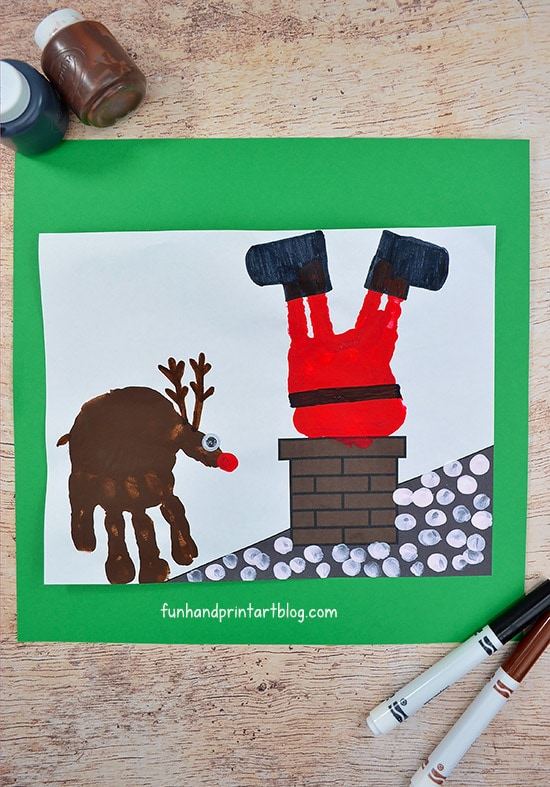 Make a stuck Santa Claus in the chimney using handprints! Free printable background included.