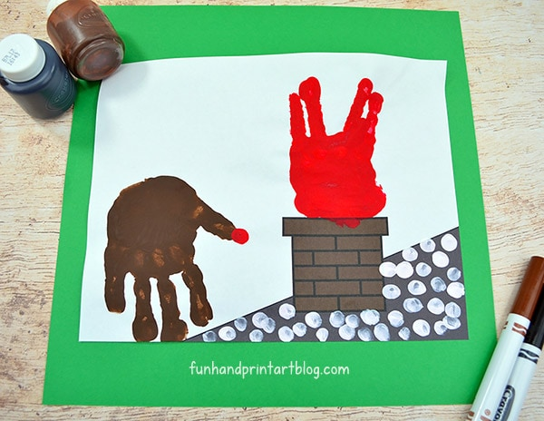 Place red handprint on top of chimney & brown handprint on the rooftop facing fingers down.