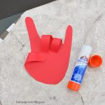 Create the 'Rock on!' handprint by folding over the two middle fingers and thumb.